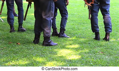 Soldiers feet with military uniform and weapons on field...