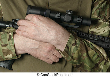 soldier's hands in camouflage hold a rifle