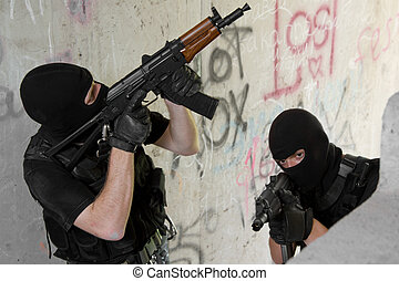 Soldiers in black masks moving upstairs with weapons