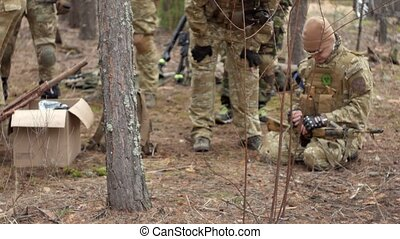 Soldiers in camouflage prepare for battle and check out...