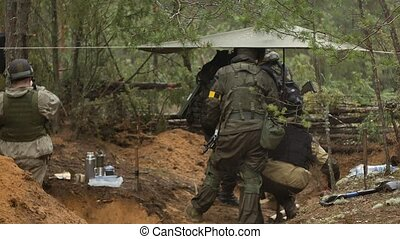 Soldiers in camouflage with combat weapons are being fired...