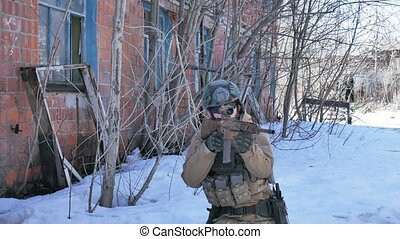 Soldiers in camouflage with combat weapons make their way...