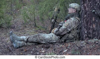 Soldiers in camouflage with military weapons rest in the...