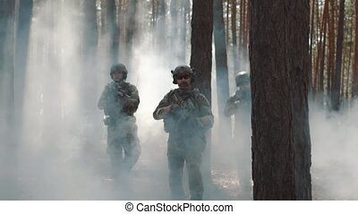 Soldiers in full ammunition takes a position in a smoky...