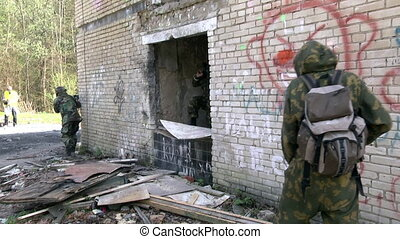 Soldiers in military uniform with weapon walk on background...