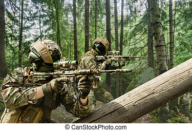 Soldiers in multicam camouflage aiming in forest.