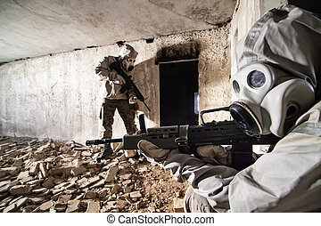 Soldiers in protective clothes and masks with the rifles on the ruined building background.