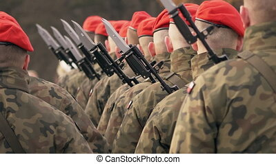 Soldiers in red berets with guns stand with their backs to...