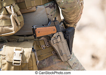 Soldiers in US Army Special Forces uniform, close up on pistol