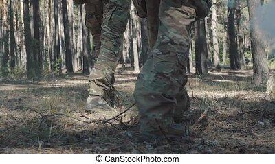 Soldier's legs walk through the forest.