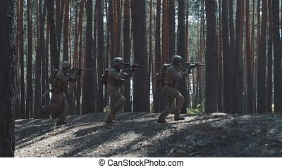 Soldiers of the US Army are running to attack in a smoky forest