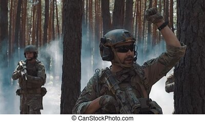 Soldiers patrol in forest - Soldiers patrol in smoky forest.