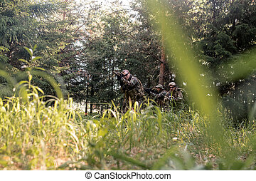 Group of armed soldiers with weapons patrolling forest in background, over grass view