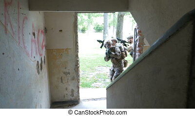 Soldiers unit entering in a ruined building checking their military objective