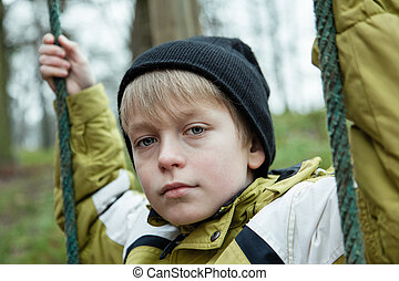 Close up view on solemn blond male child in yellow coat and black knitted hat holding on to ropes for swing set in park outdoors