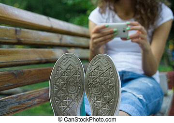 Soles shoe closeup. In the background girl in jeans using a mobile phone sitting on a bench. Rest in the park.