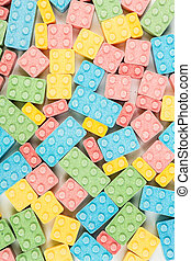 Solid background of multicolored candy building blocks