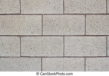 Close-up of a gray cinder block cement wall of a public school building.