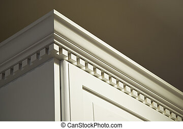 The top crown moulding dentil detail on some creme-color painted solid wood kitchen cabinets. These wall mounted cabinets do not go all the way to the ceiling above them. The lighting is coming from the top right from a ceiling light.