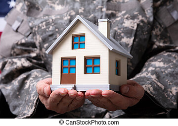 Solider Holding Model House In Hand