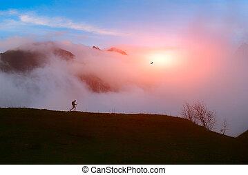 solitario, excursionista, en las montañas, en, puesta del sol con las nubes