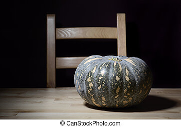 Solitary pumpkin on rustic table with chair.
