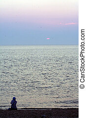Solitary Sunset - Silhouette of a woman sitting on the beach...