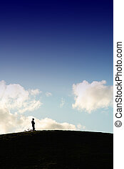Solitude - A silhouette man standing on top of the hill