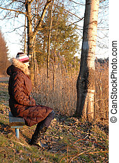 solitude - a woman alone on the bench in winter time