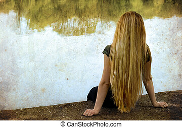 Solitude: blond woman standing alone on lakeside