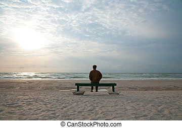 Adult man sitting alone on the bench looking at a stormy sea alone