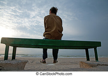 Solitude by the sea - Adult man sitting alone on the bench...