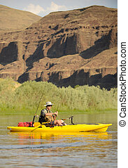 solitude man fishing in a kayak on a river in the summer