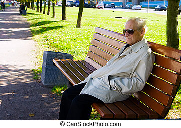 Solitude - portrait of the old man sitting alone on the...