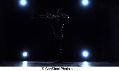 Solo concert, musician playing on trombone. Dark studio,...
