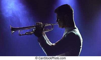 Solo concert of a male musician playing the trumpet. A talented man performs a melody of classical instrumental music in a dark studio with blue light. Side view. Close up