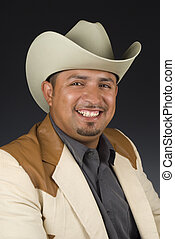 Head shot of a smiling Latino male with cowboy hat