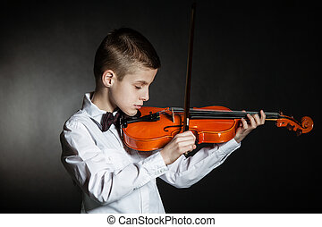 Young solo musician holds violin under his chin poised to play in a darkened room