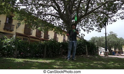 Solo Street Juggler - Street juggler practicing with green...
