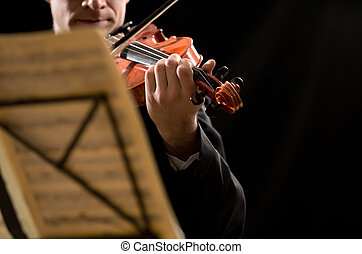 Solo violin player with sheet music and stand on foreground.
