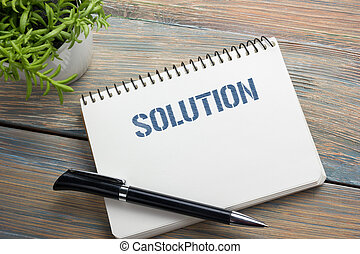 Solution. Notepad with message, pen and flower. Office supplies on desk table top view