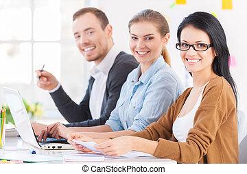 solutions., koledzy, świeży, pracujący, posiedzenie, młody, razem, do góry, radosny, ich, aparat fotograficzny, miejsce, trzy, nadchodzący, projektować, uśmiechanie się