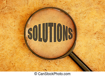 Magnifying glass focusing on the word solutions