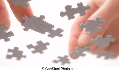 Hands Interlocking pieces of puzzle. View from below. Grey oddly shaped pieces of jigsaw. Conceptual. Metaphor of finding the solution to complicated task. Complicated relationships concept.