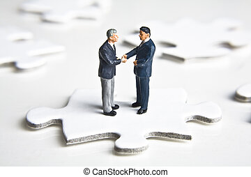 Solving the business puzzle - Businessman figurines shaking...