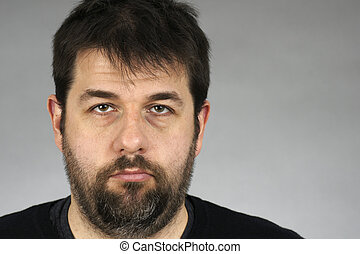 Portrait of a very serious, somber or depressed dark hair and beard middle-age man over grey bacground.