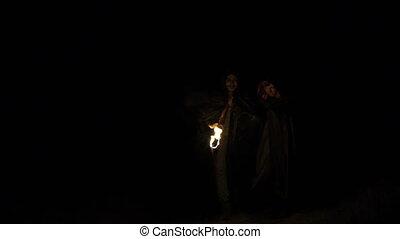 sombre, gens, brûler, forest., manteaux, courant, noir, mains, lentement