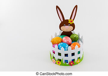 Colorful Easter eggs in a basket with an Easter bunny