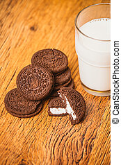 some dark glass of milk and cookies on a blurred background