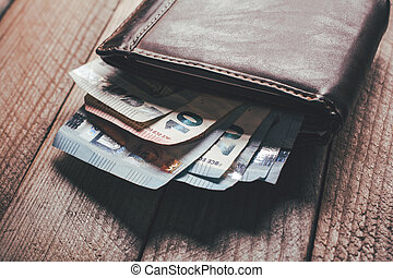 Some Euro Banknotes Showing Out Of Brown Leather Wallet On A Wooden Board Viewing From The Side